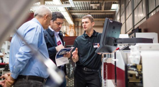 Men discussing Mark Andy printer