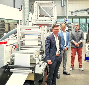 Members of Mark Andy and Barthe Group in front of Mark Andy press